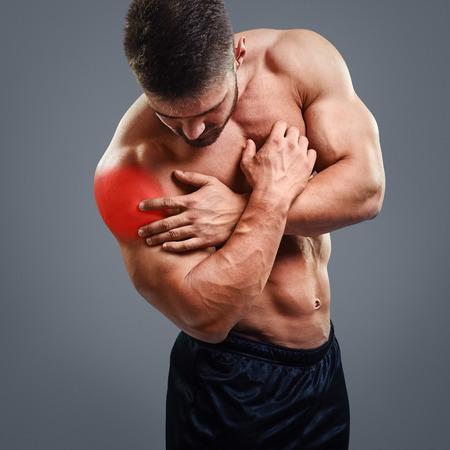 灰色の背景の上の肩の痛みでボディービルダー。強調表示された赤くスポットのコンセプト。