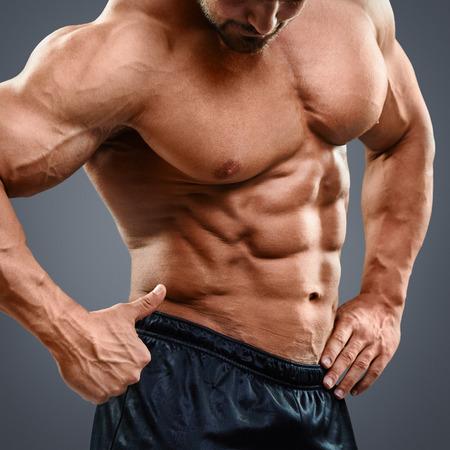 Homem muscular com músculos do tronco bonita que mostra o sinal aprovado. Mediana do homem descamisado apontando para abs isolada no fundo cinzento