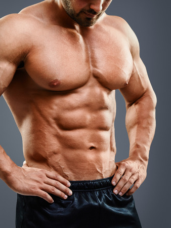 hombres sin camisa: musculoso pecho y los abdominales perfectos. Imagen recortada de hombre musculoso de pie aislado en fondo gris Foto de archivo