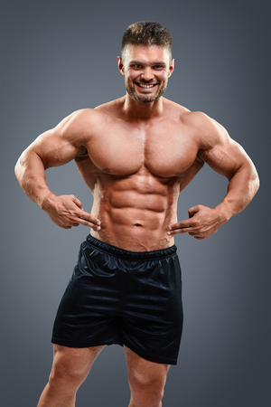 muscular body: Midsection of shirtless man pointing at abs against black background