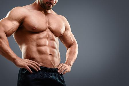 Perfeito peito musculoso e abs. Imagem colhida do homem muscular em pé isolado no fundo cinzento Banco de Imagens