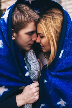 Pares novos que afagam e escondido debaixo de uma manta. casal moderno no amor