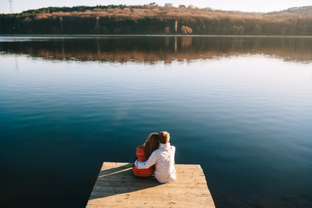 A young teens couple dreaming on the wooden jetty at a lake on a cold autumn day