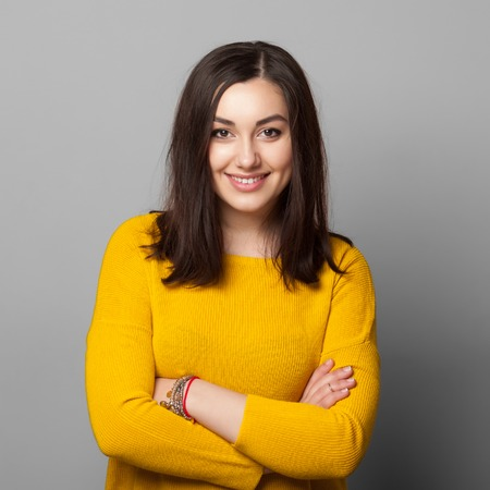 Smiling business woman with folded hands against grey background. Toothy smile, crossed arms. Stock fotó