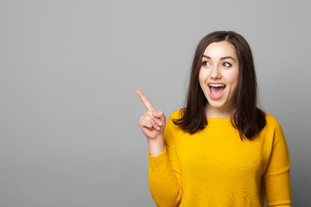 Excited young woman pointing her finger towards blank space isolated over grey background