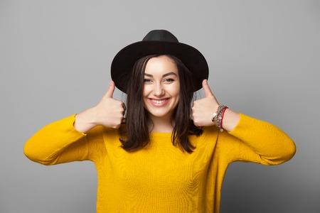 Портрет модный молодой женщины, показывая пальцем вверх на сером фоне