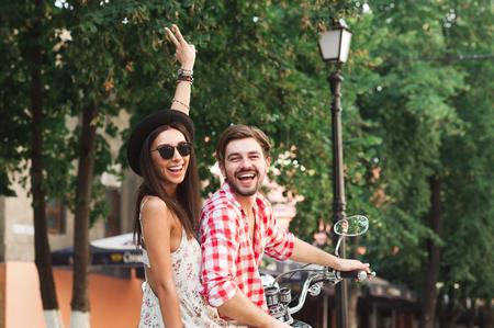 Vista traseira de jovens desgastando dos pares roupas elegantes felizes sentadas em scooter, posando e sorrindo em um dia de ver Banco de Imagens