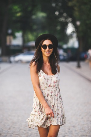 summer dress: Beautiful brunette young woman wearing dress and walking on the street