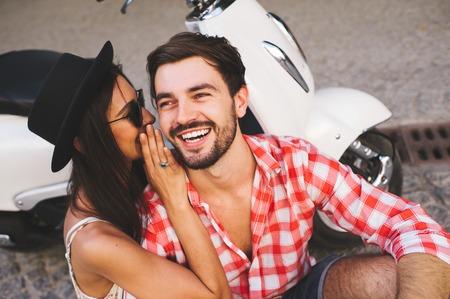 Крупным планом привлекательная молодая пара whipsering к уху секрет, сидя возле скутера и улыбается. Счастливый концепция relathionship