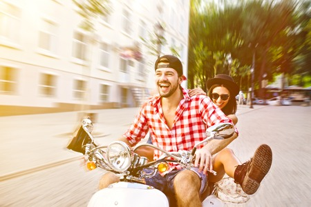 scooter: pareja joven y despreocupado que monta un scooter en el calles de la ciudad. efecto de desenfoque velocidad.