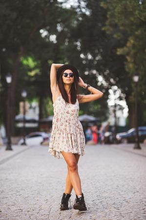 cuerpo femenino: Hermosa mujer joven posando en una calle al atardecer. foto de cuerpo completo del modelo con un vestido de verano y