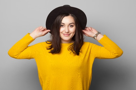 Brunette elegante vestindo roupas amarelas brilhantes que prendem o chapéu com os olhos fechados isolados no fundo cinzento