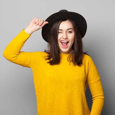 Menina adolescente positiva alegre novo que dá uma piscadinha para a câmera isolada no branco. Estilo de vida conceito despreocupado. Banco de Imagens