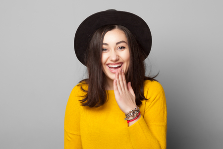 Lovely young woman with shy mistake gesture looking at you on grey background isolated