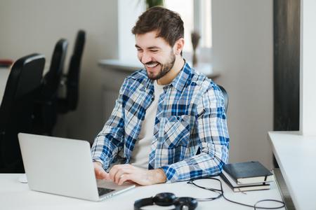 hombre escribiendo: joven apuesto hombre feliz que usa la camisa ocasional de trabajo en la computadora portátil en la oficina y sonriente