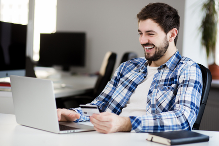 online purchase: Smiling young man doing online shopping through laptop and credit card in office Stock Photo