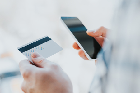 クローズ アップ若い男の手のセルを使用し、クレジット カードを保持、オンライン ショッピングや報告用スマート フォンを失ったカード、不正な