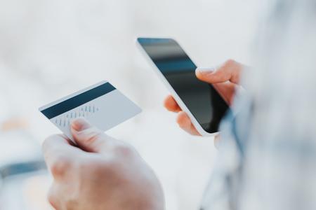 pagando: hombre joven del primer de las manos que sostienen la tarjeta de crédito y uso de teléfono, teléfono inteligente para ir de compras en línea o informar tarjeta perdida, transacción fraudulenta Foto de archivo