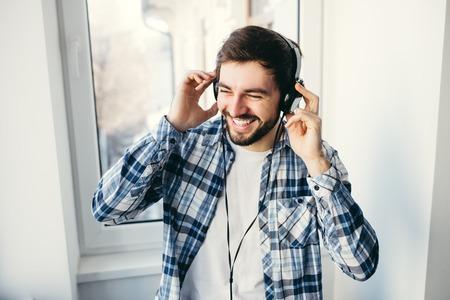 Retrato de um homem jovem e bonito com fones de ouvido, sorrindo e ouvindo m