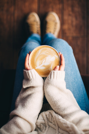 girl sitting: Close up of girls hands holding a cup of coffee indoors. Top view and feet Stock Photo