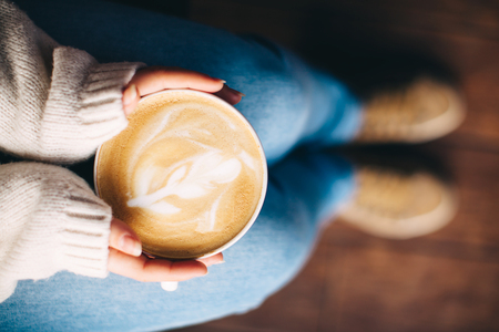 autumn food: Close up of girls hands holding a cup of coffee indoors. Top view,