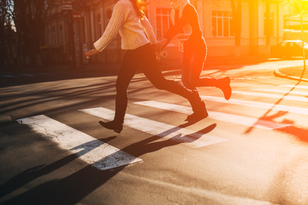 Abstract concept of couple running  together to cross the road. Banco de Imagens