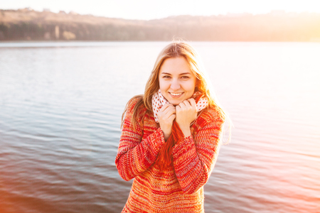 shy girl: Happy young girl wearing warm clothes standing and smiling by a lake. Sun light at sunset. Stock Photo