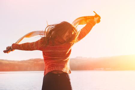 siluetas mujeres: Chica joven positiva vistiendo ropa de invierno caliente que se divierten en el lago. Foto de archivo