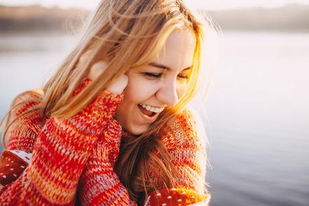 Крупным планом битник застенчивая девушка носить теплую одежду стоя и улыбается на берегу озера. Солнечный свет на закате.