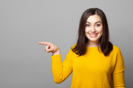 smiling young woman pointing finger away isolated on a grey background