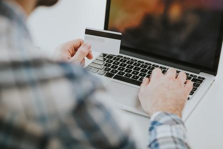 tarjeta visa: Vista trasera de las manos masculinas que sostienen la tipificación de tarjetas de crédito en el teclado del ordenador portátil.