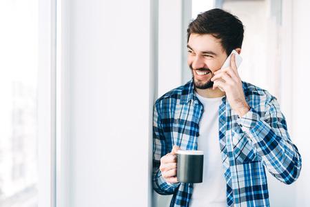 hablando por celular: Hombre joven con ropa casual hablando por un teléfono móvil en la mañana en una ventana con espacio de copia, Foto de archivo