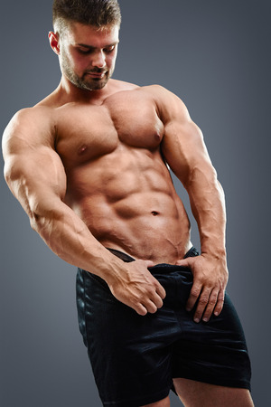 shirtless man showing his abdominal muscles against grey background 版權商用圖片