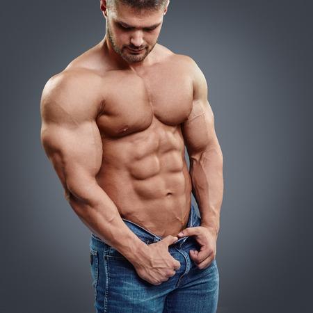 shirtless: musculoso pecho y los abdominales perfectos. Imagen recortada de hombre musculoso de pie aislado en fondo gris Foto de archivo