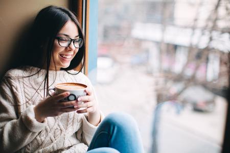 chicas sonriendo: linda chica hermosa en el caf� cerca de la ventana con la sonrisa del caf�