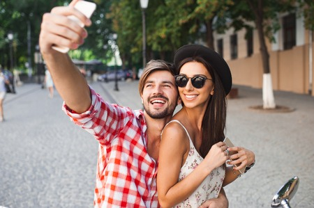 young love: couple making selfie photo on a background of the city