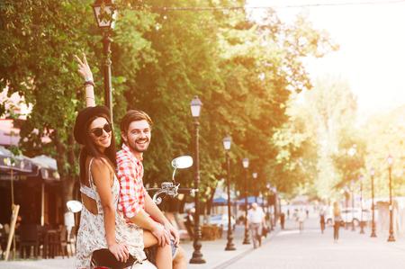 glamorosa joven pareja feliz montando un scooter vintage en la calle, la mujer lleva un sombrero y gafas de sol Foto de archivo