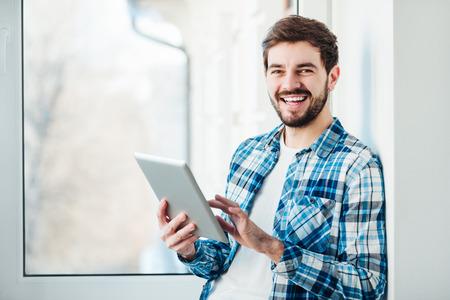 Счастливый молодой человек улыбается в камеру с планшетом в руках