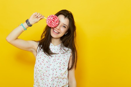 lollipop: happy modern teenage woman smiling and hiding behind a lollipop candy over yellow background Stock Photo