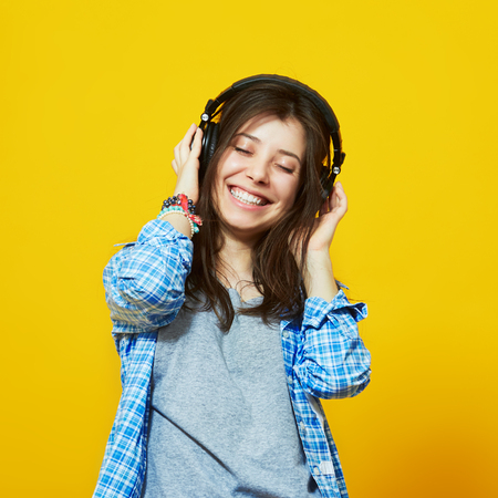 Young woman with headphones listening to music. Teenager girl enjoying music against isolated over yellow background 版權商用圖片