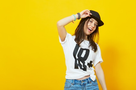 Cool teenage girl in hip hop outfit wearing a t-shirt and cap leaning against a yellow wall with copy space