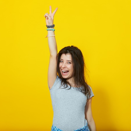 two persons: Happy smiling beautiful young woman showing two fingers or victory gesture, isolated over yellow background Stock Photo