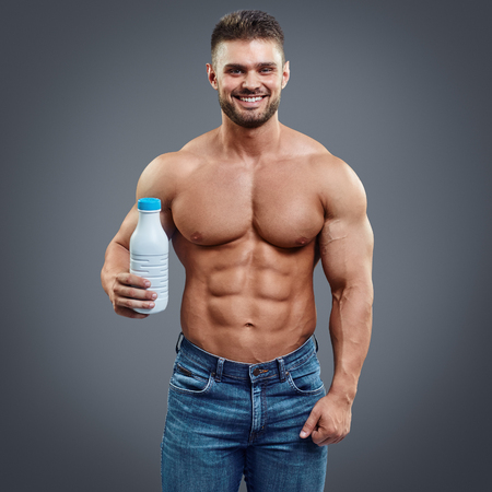 body milk: milk bottle in the hands of a sports person. Bodybuilder with strong body holding a bottle of milk in his hand over grey background Stock Photo