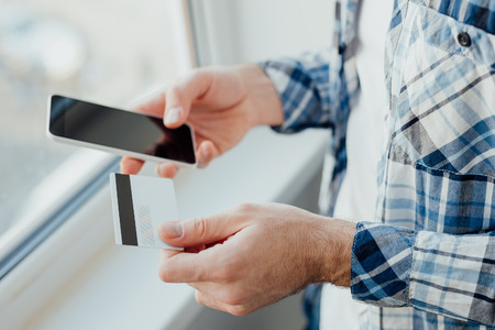 cvv: Mans hands holding a credit card and using smart phone for online shopping Stock Photo