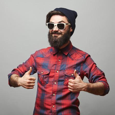 Улыбается молодой человек с длинными волосами лица, давая пальцы вверх знак. Счастливый человек хипстер с бородой и солнцезащитные очки, показывая хорошо жест.