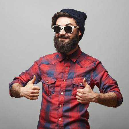Smiling young man with long facial hair giving thumbs up sign. Happy hipster man with beard and sunglasses showing ok gesture.