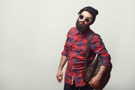 Fashion portrait of bearded hipster young man wearing sunglasses, backpack and hat over grey background with copyspace. Confident man with beard.