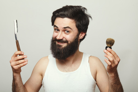 depilate: Bearded young man holding retro shaving tools in his hands isolated over grey background