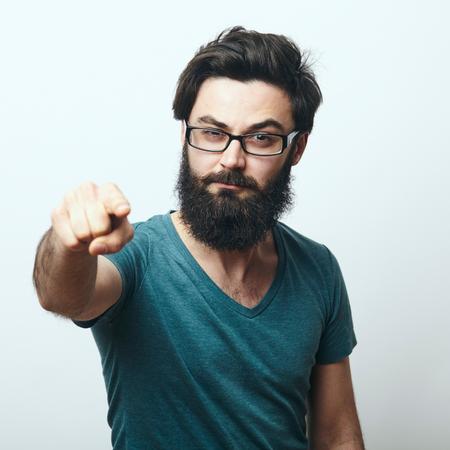 カメラに指を指して眼鏡の若いひげを生やした男の肖像画。我々 は、概念を必要があります。プログラマは、IT 専門のカメラを指しています。