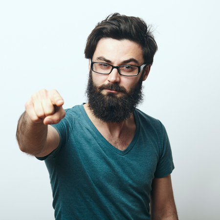 Portrait of young bearded man with glasses pointing his finger to the camera. We need you concept. Programmer, IT specialist pointing to camera.